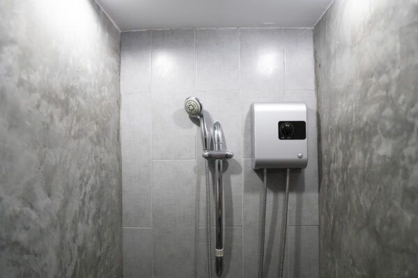 Instant tankless electric water heater installed on grey tile wall with input and output pipe outlet and elcb safety breaker system and silver shower