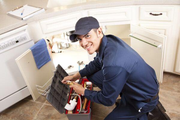 Latin Plumber working under sink in kitchen. Service industry. Home repairman.