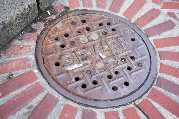 Distressed sewer manhole cover on brick city street.
